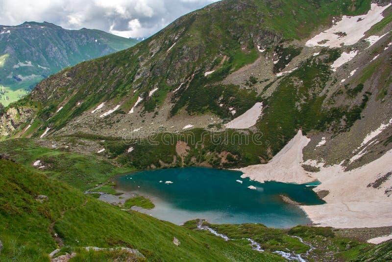 Una vista superiore di un lago verde smeraldo della montagna con un cappuccio della neve circondato dai pendii di montagna verdi immagine stock