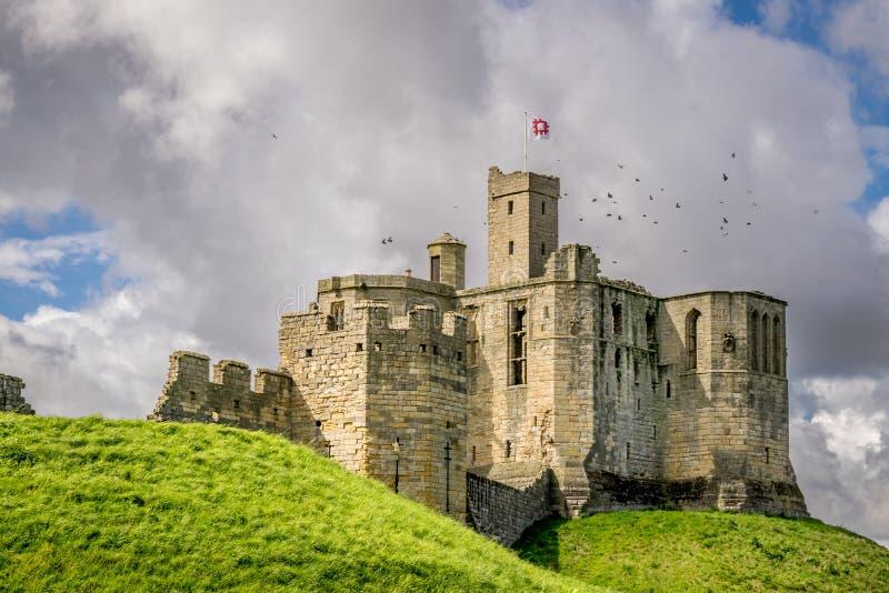 Una vista un castello antico su una collina verde immagini stock
