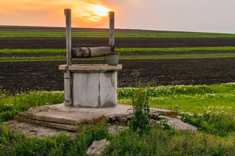 Una vista a un pozo de drenaje cerca un campo durante amanecer fotos de archivo libres de regalías
