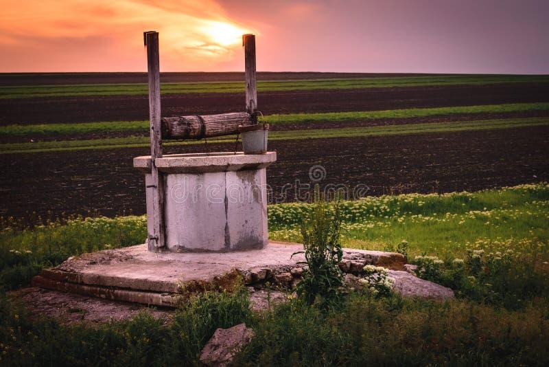 Una vista a un pozo de drenaje cerca un campo durante amanecer imágenes de archivo libres de regalías
