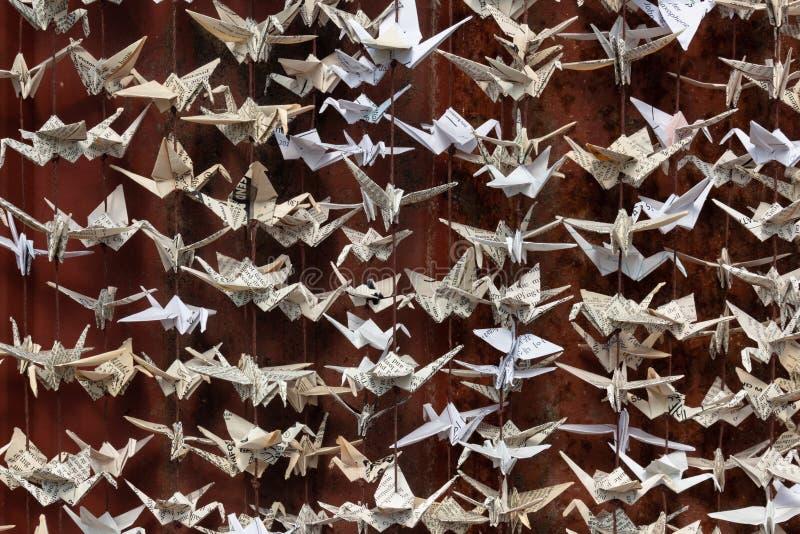 Una vista vicina stessa di 1000 origami ha piegato la scultura di carta delle gru contro un fondo di vecchio raccordo rosso della immagini stock libere da diritti