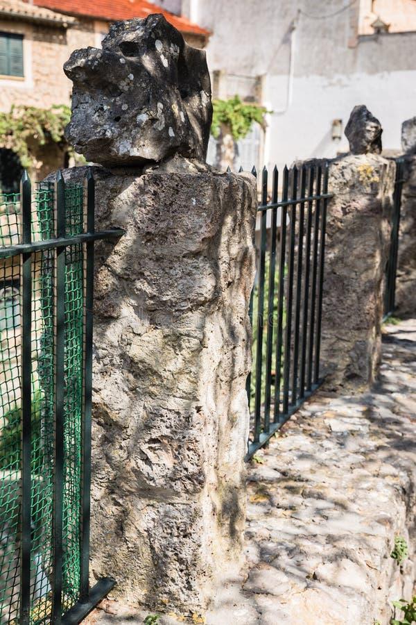 Una yarda alrededor de la casa con los postes concretos con las piedras en los extremos fotografía de archivo