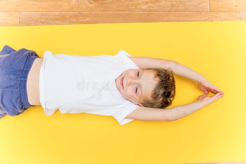 Una yoga practicante del niño pequeño en casa imagenes de archivo