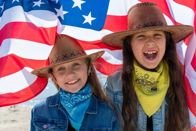 Unabh?ngigkeit Day Patriotischer Feiertag Gl?ckliche Kinder, nette zwei M?dchen mit amerikanischer Flagge cowboy USA feiern Juli  lizenzfreie stockfotos