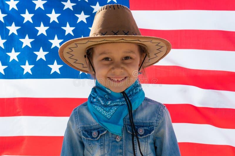 Unabh?ngigkeit Day Patriotischer Feiertag Gl?ckliches Kind, nettes kleines Kinderm?dchen mit amerikanischer Flagge cowboy stockbild