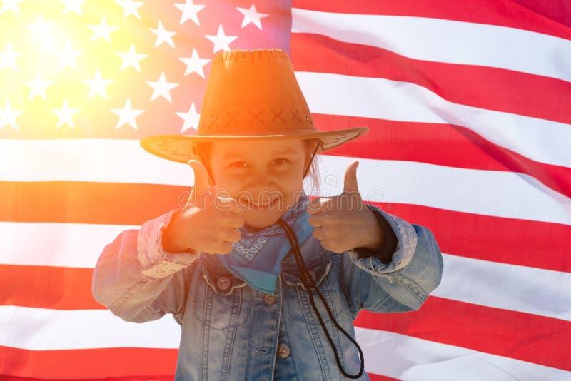 Unabh?ngigkeit Day Patriotischer Feiertag Gl?ckliches Kind, nettes kleines Kinderm?dchen mit amerikanischer Flagge cowboy stockfotografie