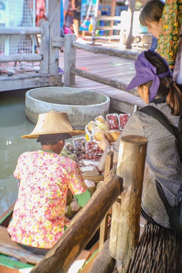 Unacquainted тайские люди продавая свежие фрукты на шлюпке в рынке Паттайя плавая стоковое изображение