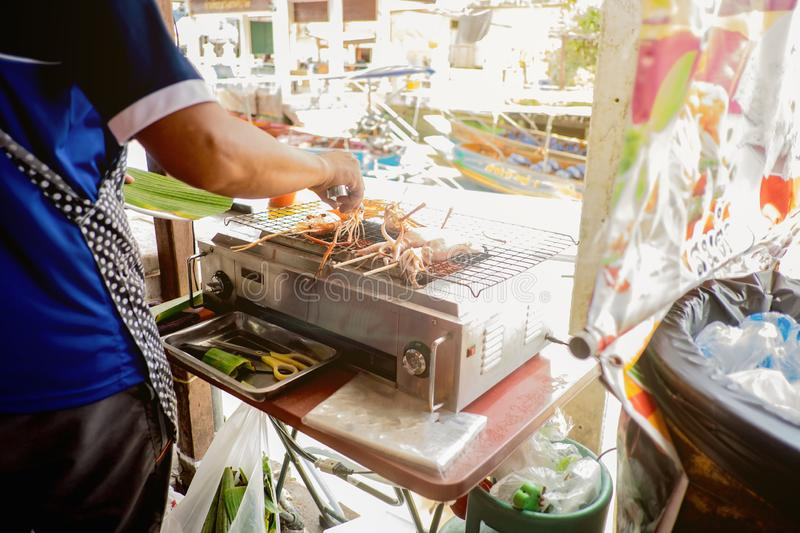 Unacquainted People selling Grilled sea food beside the river in Amphawa Floating market in holiday time. Amphawa Floating market is very Famous Floating market royalty free stock photos
