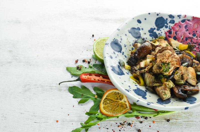 Unagi Salad with chicken, mushrooms, vegetables and pumpkin seeds. On a wooden background. royalty free stock photography