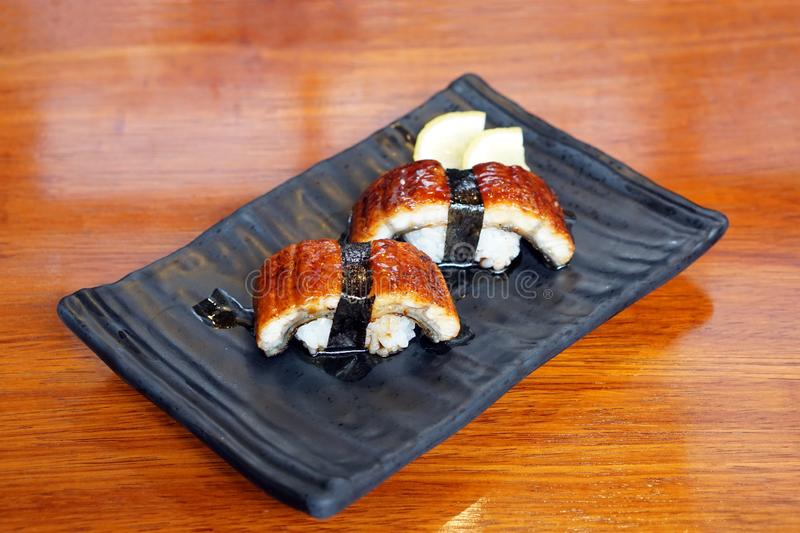 Unagi sushi - A plate of steamed rice topped with grilled freshwater eel and sweet sauce. on wooden table. royalty free stock images