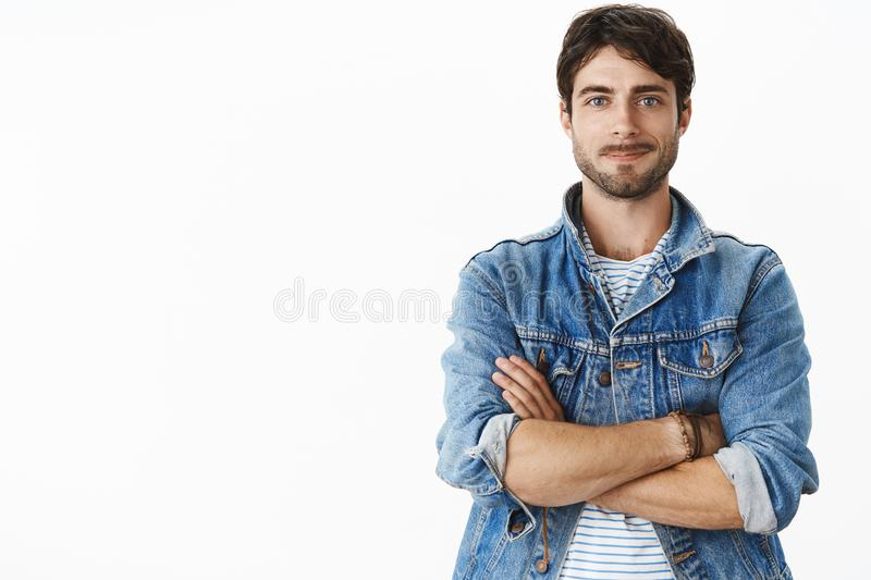 Unaltered shot of charismatic handsome hot adult man with beard and blue eyes in stylish denim jacket over striped t royalty free stock images