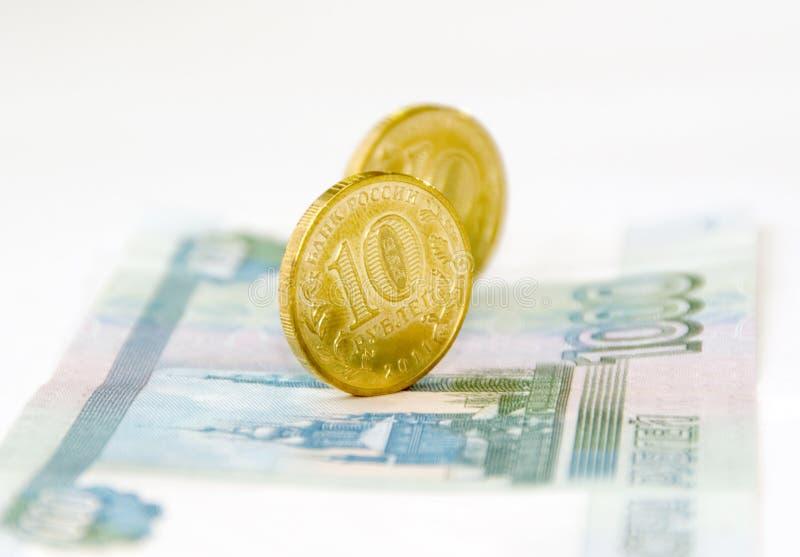 Unas par de monedas en un billete de banco imagen de archivo libre de regalías