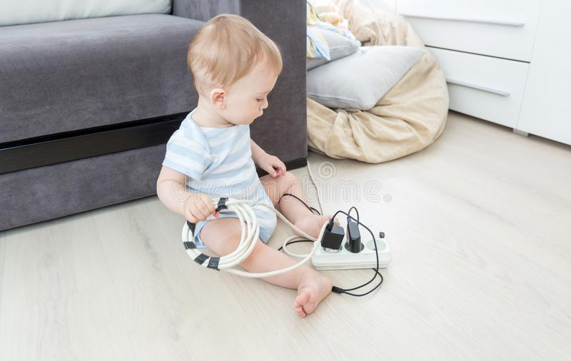 Unatteded little baby boy playing with electric power cables. Child in dangerous situation. Unatteded little baby playing with electric power cables. Child in royalty free stock photos