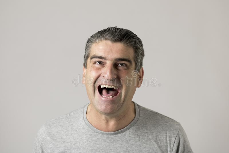 Unattractive 40s or 50s white funny man in sick and mad happy face expression screaming and shouting crazy isolated on grey royalty free stock image