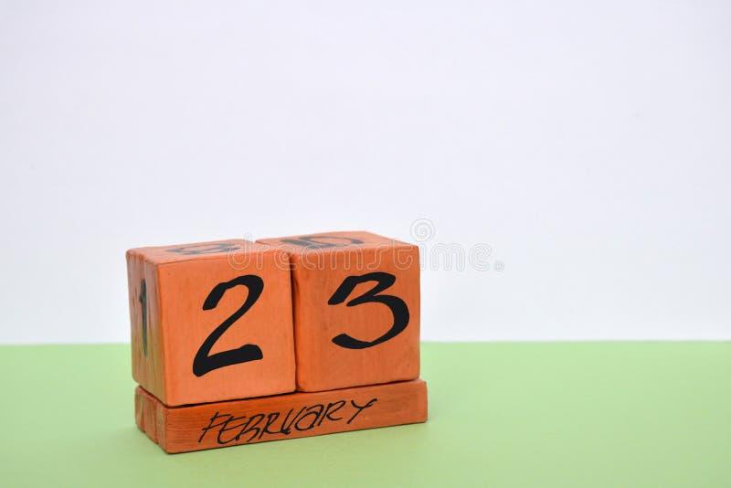 Unaufhörlicher hölzerner Kalender mit Datum der vom 23. Februar herein Ecke auf weißem grünem Hintergrund Konzept des Verteidiger stockfotos