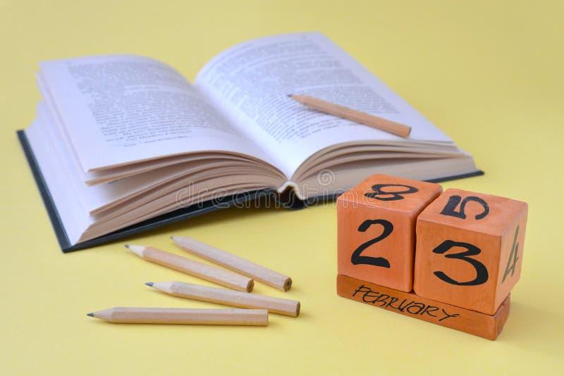 Unaufhörlicher hölzerner Kalender mit Datum vom 23. Februar, einem geöffneten Buch und Bleistiften auf einem gelben Hintergrund m stockfotografie