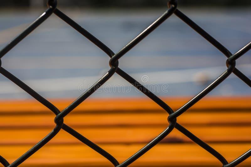 Unaufhaltsame warme Farbe, orangerote Bank durch den Freiluftzementbasketballplatz innerhalb des Stacheldrahts stockbilder