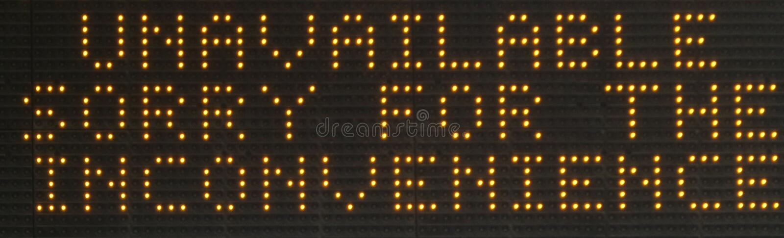 `Unavailable` LED dot matrix sign display. Dot matrix sign of LED lamp bulbs displaying the message `Unavailable sorry for the inconvenience`. Zoomed in on a royalty free stock photos