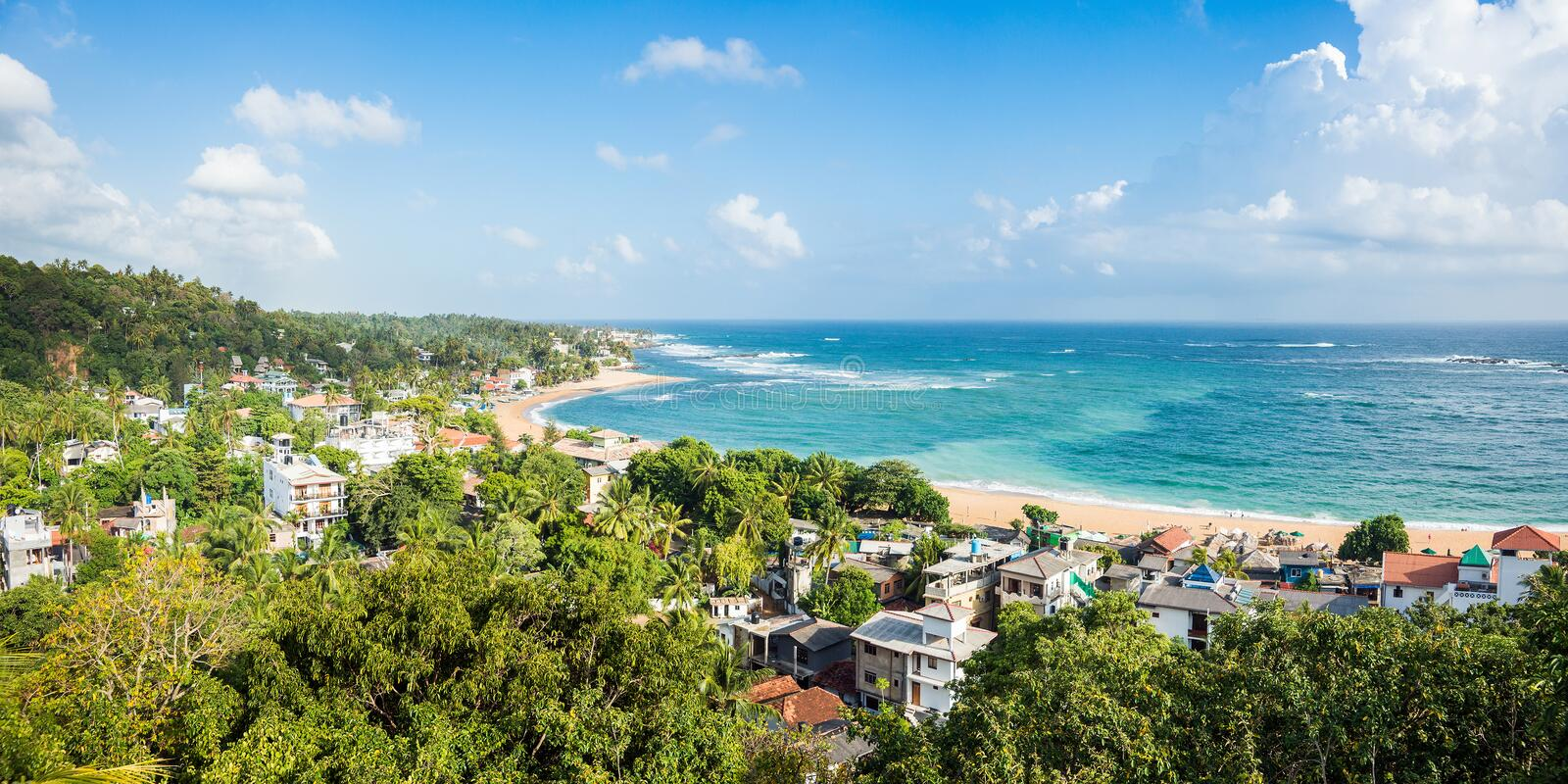 Unawatuna beach at sunny day. Panoramic view from rooftop hotel royalty free stock photo