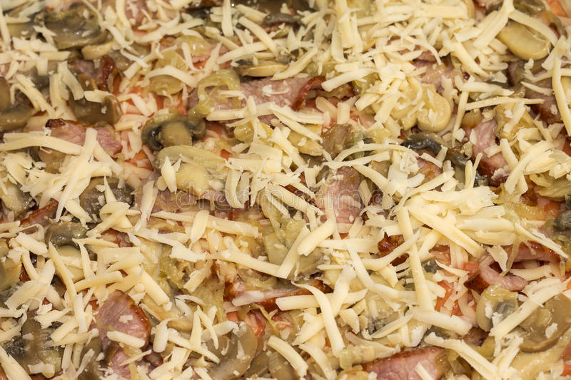Unbaked pizza with bacon and mushrooms, close-up royalty free stock photo