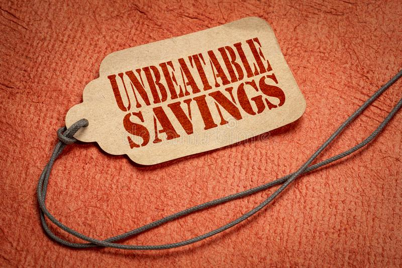 Unbeatable savings text  on price tag. Unbeatable savings text on a paper price tag with a twine against textured bark paper royalty free stock photos