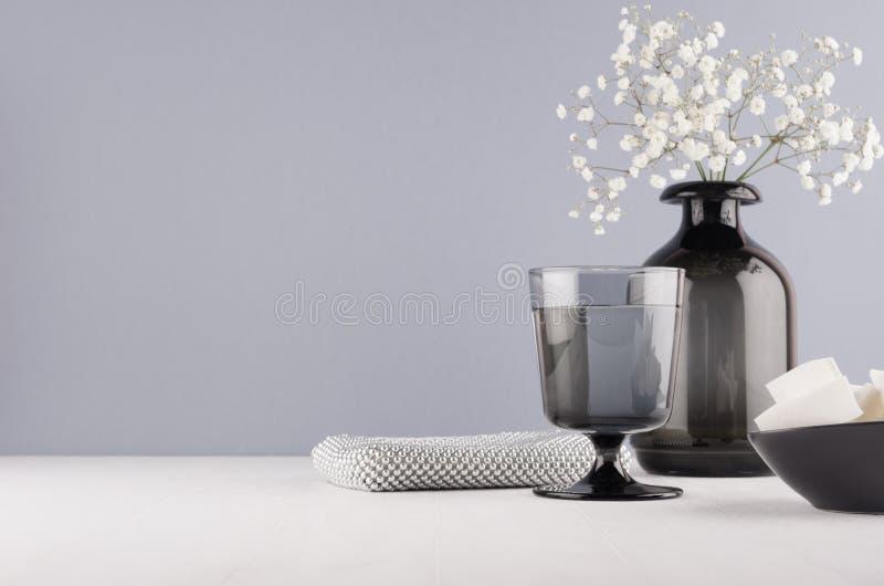 Unbedeutendes Innenbadezimmer in der einfarbigen grauen Farbe - schwarzer Glasvase mit kleinen weißen Blumen, Becher, silberne Ko stockfoto