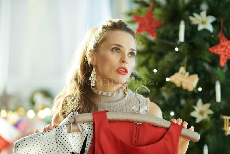 Unbefriedigte Hausfrau, die festliche Weihnachtsausstattung vorwählt stockfotos