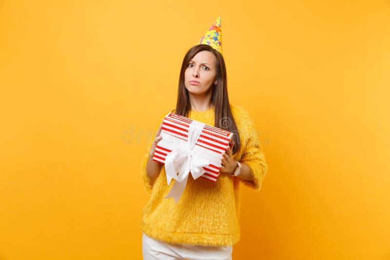 Unbefriedigte umgekippte junge Frau im Geburtstagsfeierhut, der roten Kasten mit Geschenk, anwesendes Feiern lokalisiert auf hell stockfotografie