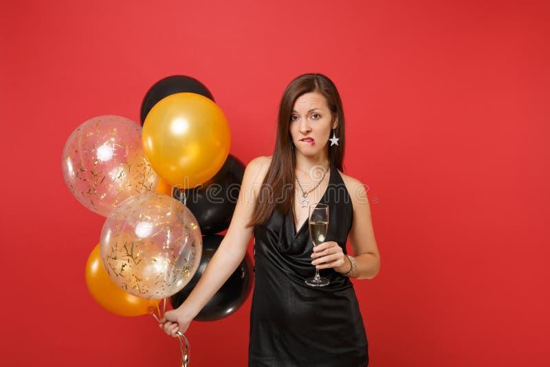 Unbefriedigtes junges Mädchen im schwarzen Kleid feiernd, ihre Lippen beißend, die Glas Champagnerluftballone an lokalisiert halt lizenzfreie stockfotos