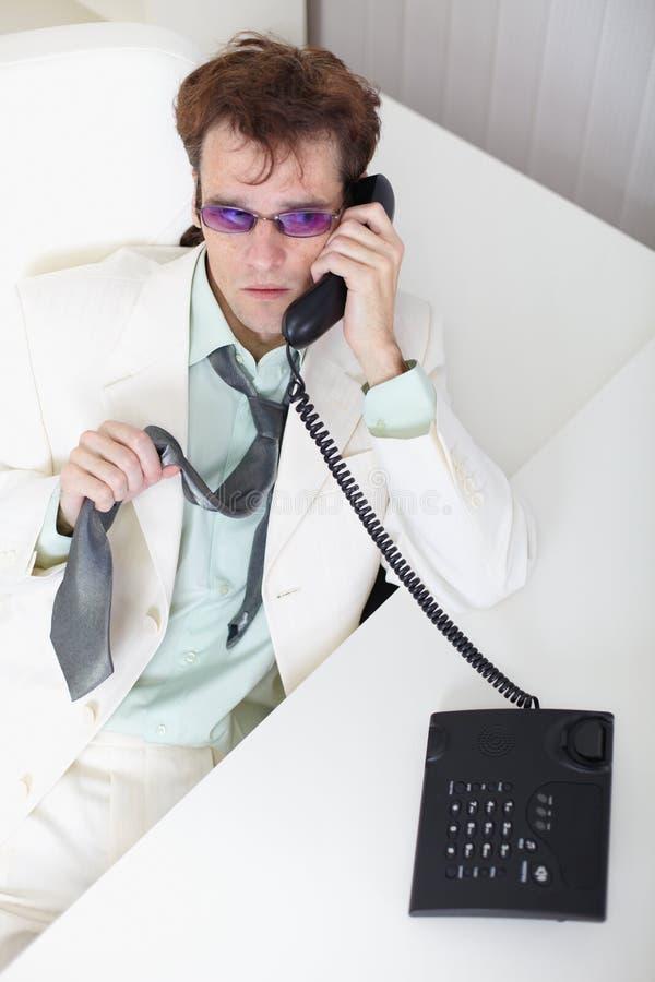 Unbehaglicher junger Geschäftsmann spricht am Telefon stockbild