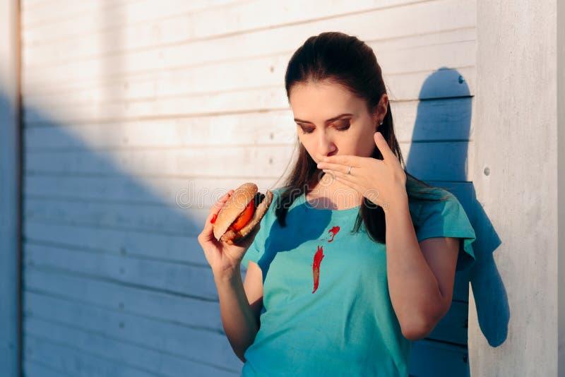 Unbeholfene Frau, die ihr Hemd mit Ketschup-Soße befleckt lizenzfreie stockfotografie