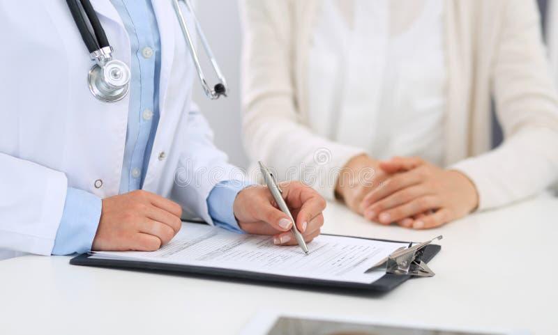 Unbekannte Ärztin und weiblicher Patient, die etwas bei der Stellung nahe Aufnahmeschreibtisch im Notkrankenhaus bespricht stockfotografie