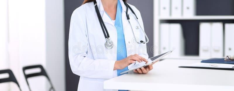 Unbekannte Doktorfrau bei der Arbeit Weiblicher Arzt, der digitale Tablette bei der Stellung nahe Aufnahmeschreibtisch an der Kli lizenzfreies stockfoto