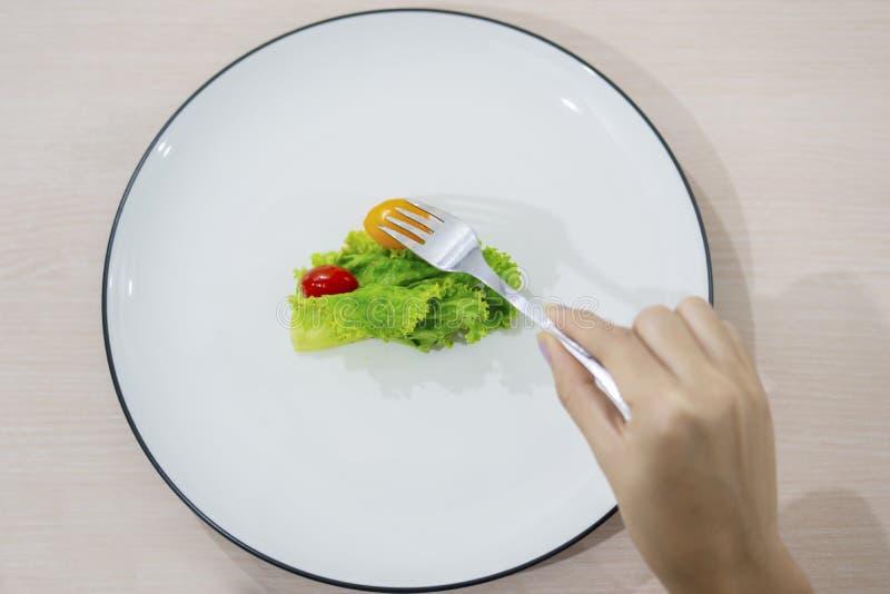 Unbekannte Frau isst kleinen Teilsalat lizenzfreie stockfotografie