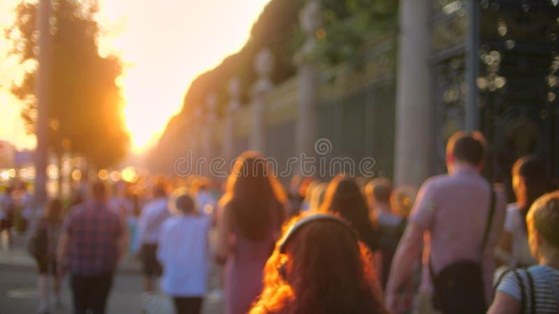Unbekannte Leute in der zufälligen Kleidung gehen bei Sommersonnenuntergang Gedrängter Bürgersteig nahe Stadtpark lizenzfreie stockfotos
