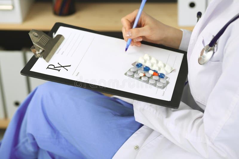 Unbekannte ?rztin bei der Arbeit am Krankenhaus Pillen am medizinischen Klemmbrett Junger weiblicher Arzt Verordnung schreiben od stockfotos