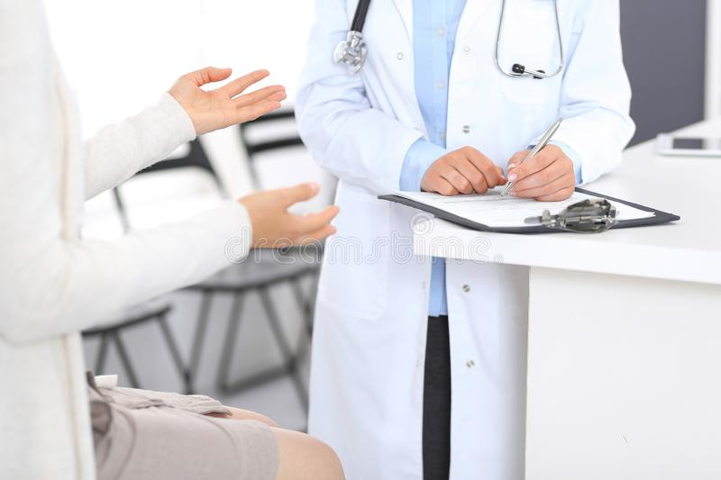 Unbekannter Doktor und weiblicher Patient, die etwas bei der Stellung nahe Aufnahmeschreibtisch im Notfall-hospit bespricht lizenzfreie stockfotografie