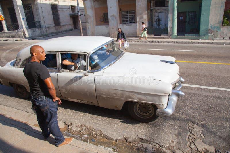 Unbekannter Kubaner nahe einem Retro- Taxi auf den Straßen eines gefährlichen Bereichs von Serrra stockfoto