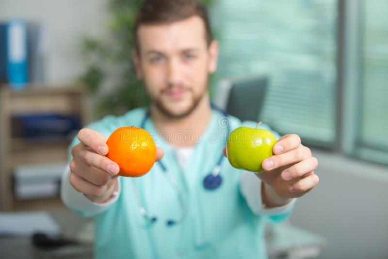 Unbekannter Mediziner oder Doktor, die Apfel und Orange halten lizenzfreie stockbilder
