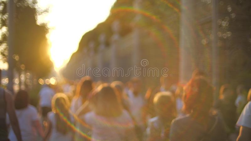 Unbekannter Weg der jungen Leute entlang der Straße bei Sonnenuntergang lizenzfreies stockbild