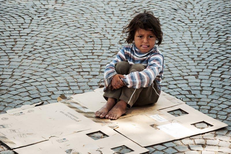 Unbekanntes obdachloses Kind, das auf der Straße sitzt stockfotografie