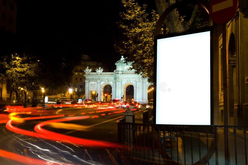 Unbelegte Anschlagtafel in einer Stadt-Nacht lizenzfreie stockfotos