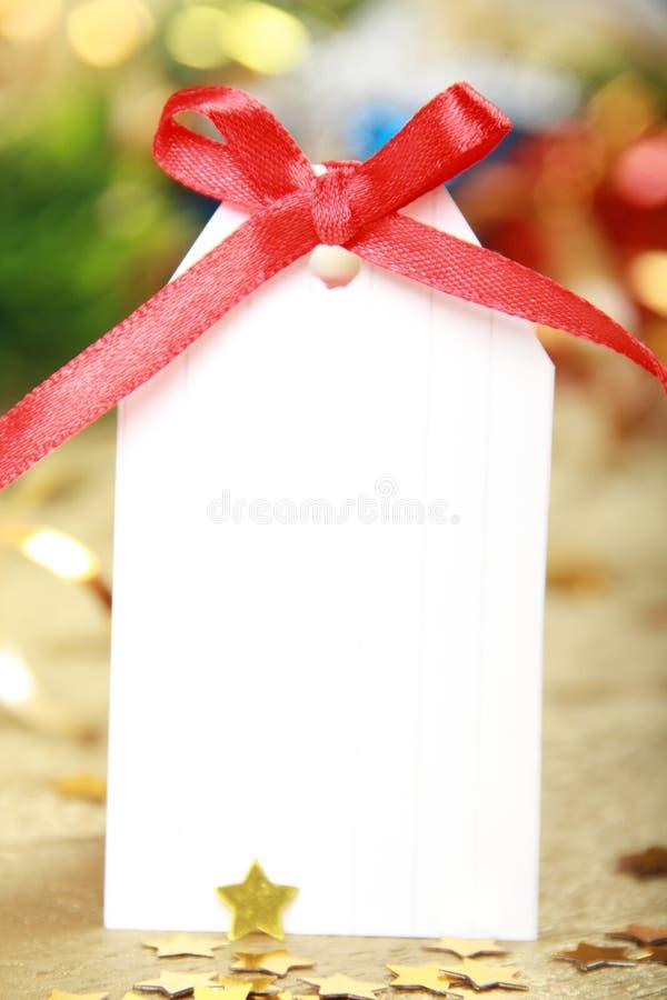 Unbelegte Geschenkmarke gebunden mit einem Bogen des roten Satinfarbbands stockfotos