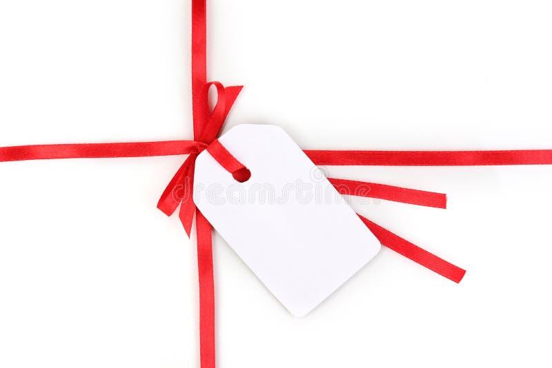 Unbelegte Geschenkmarke mit Bogen auf rotem Satinfarbband stockfotografie