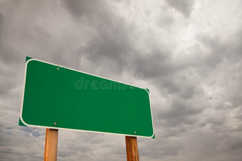Unbelegtes grünes Verkehrsschild vorbei Sturm-Wolken stockfoto