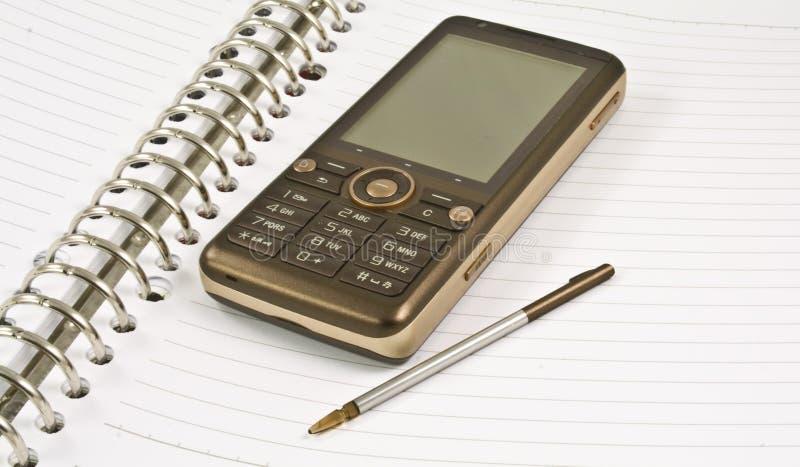 Unbelegtes Notizbuch, Stift, Handy stockbild