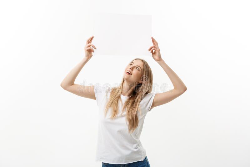Unbelegtes Zeichen Frau, die leeres leeres weißes Zeichen über ihrem Kopf hält Aufgeregte und glückliche schöne junge Frau an lok stockfotografie