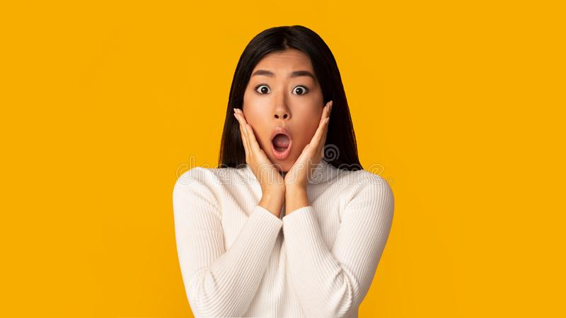 Unbelievable! Shocked girl with open mouth and hands on cheeks royalty free stock photos