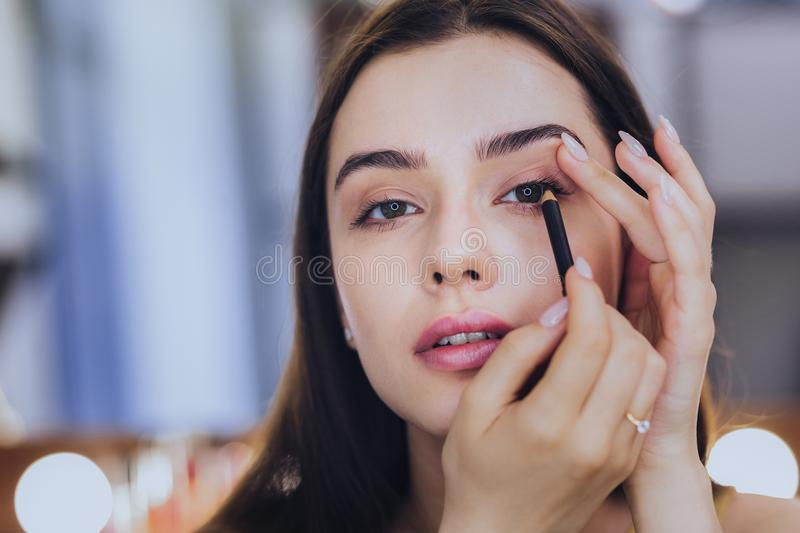 Unbelievably beautiful woman using black eyeliner. Black eyeliner. Unbelievably beautiful young dark-haired woman using black eyeliner while putting makeup on royalty free stock photo