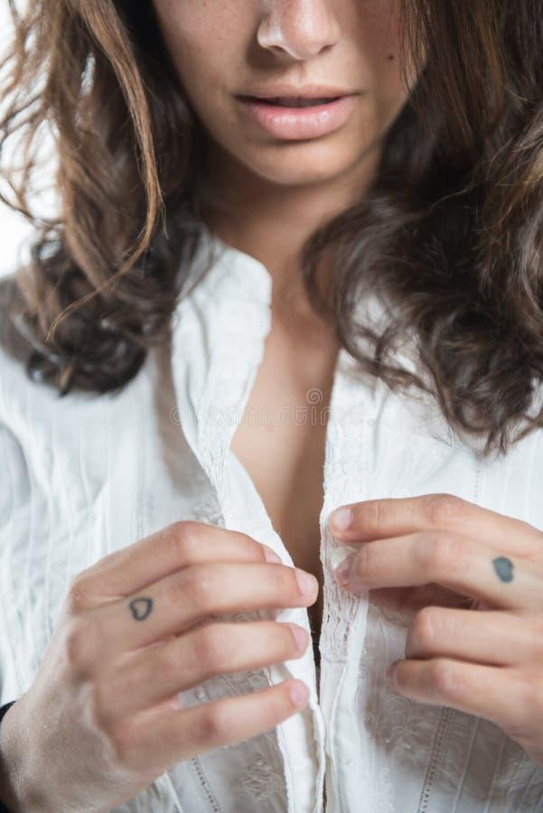 unbottoning她的白色衬衫的美丽的年轻女人 库存图片